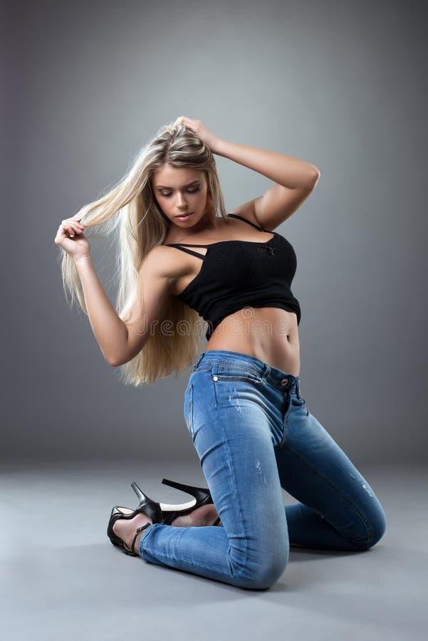 Het verbazende sexy vrouw stellen in zwarte en jeans royalty-vrije stock foto's