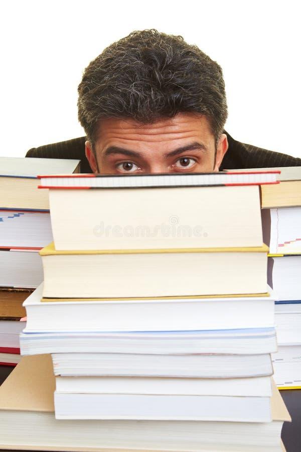Het verbergen achter boeken royalty-vrije stock afbeeldingen