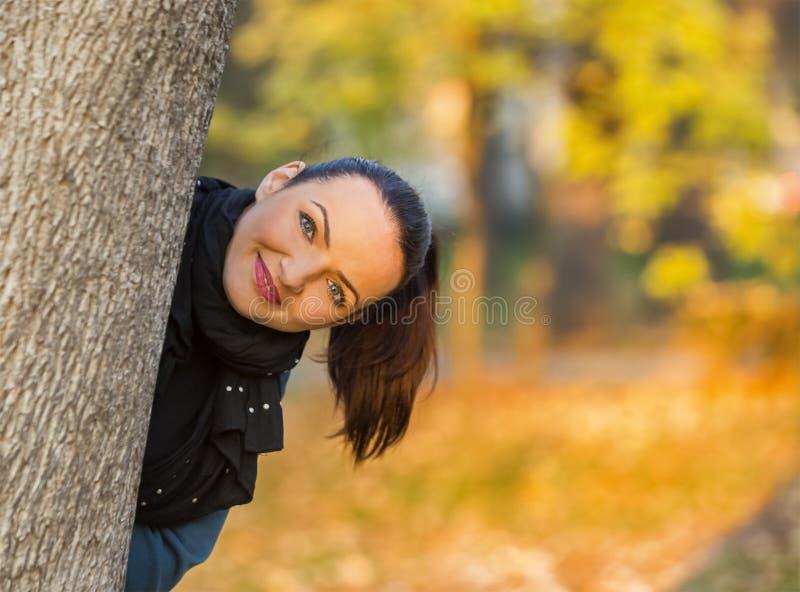 Het verbergen van de vrouw achter een boom stock foto