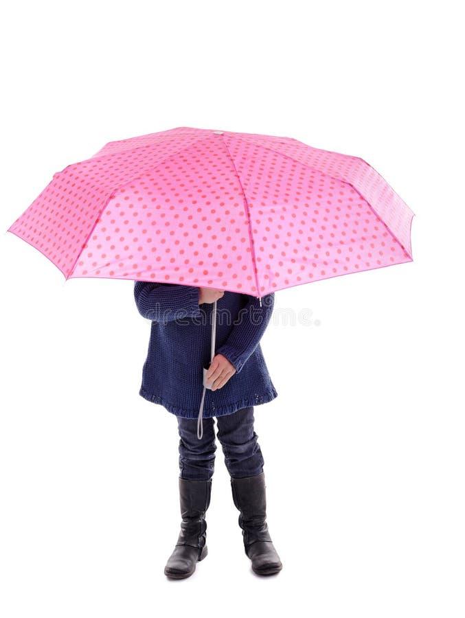 Het verbergen van het meisje onder een roze met puntenparaplu stock foto's