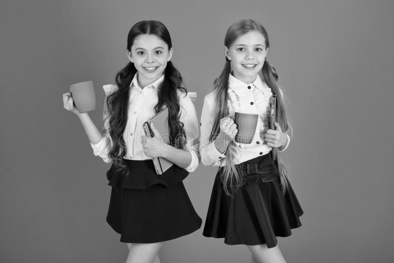 Het verbeteren van hun energie en stemming De kleine meisjes genieten van de Leuke schoolmeisjes die van het schoolontbijt koppen royalty-vrije stock foto