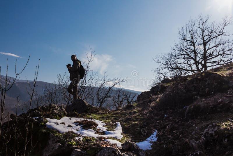 Het verblijf van het mensensilhouet op scherpe rotspiek Stel wandelaar tevreden genieten van mening royalty-vrije stock afbeeldingen