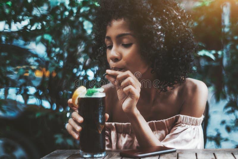 Het verblinden van biracial meisje drinkt in openlucht een cocktail royalty-vrije stock foto