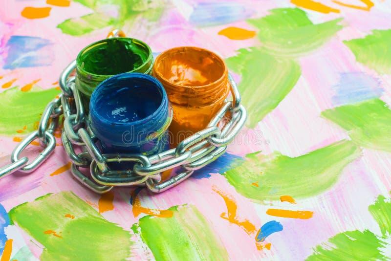 Het verbod op creativiteit, wordt drie blikken van verf ineengestrengeld met een metaalketting, een multicolored achtergrond royalty-vrije stock afbeelding