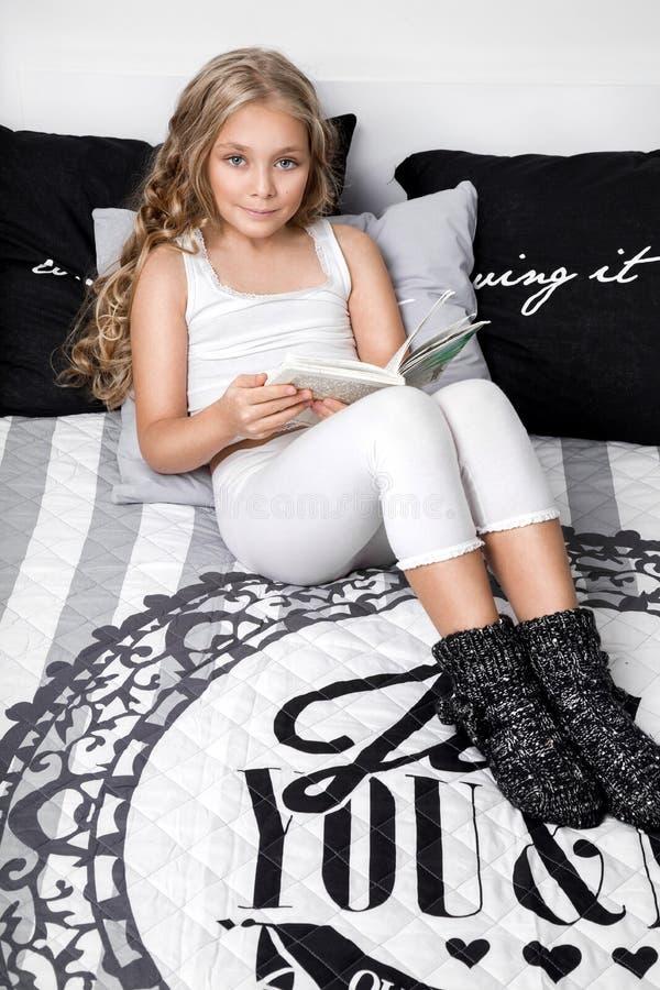 Het verfijnde jonge mooie blonde meisje, weinig prinses met lang haar en blauwe ogen, het kind liggen in bed stock afbeelding