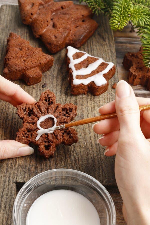Het verfraaien van de chocoladekoekjes van de Kerstmispeperkoek met witte ic royalty-vrije stock foto's