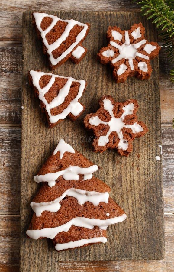 Het verfraaien van de chocoladekoekjes van de Kerstmispeperkoek met witte ic stock foto's