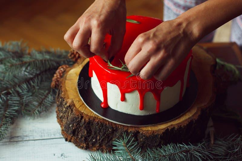 Het verfraaien van proces van de eigengemaakte cake van Kerstmis rode ganache door vrouwen` s handen met rozmarine en rode bessen stock afbeeldingen
