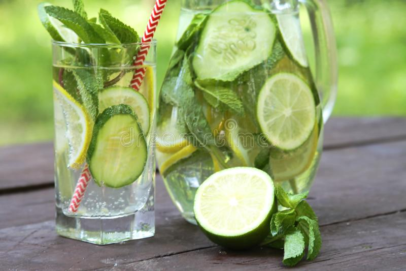 Het verfrissen van Sassy water van de zomer het koude dranken met citroen, kalk, komkommer, munt, gember in glas en kruik op hout stock foto