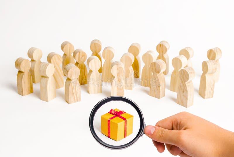 Het vergrootglas bekijkt de grote groep mensen die een gift bekijken kiezend een goede gift, een beperkt aantal, uitgever*kopt al stock afbeelding