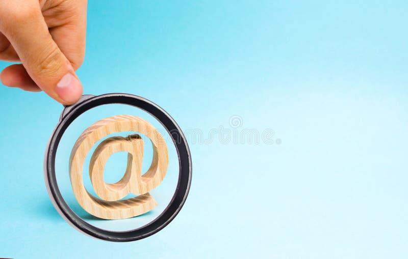 Het vergrootglas bekijkt de Internet-correspondentie, mededeling over Internet E-mailpictogram op blauwe achtergrond royalty-vrije stock afbeelding