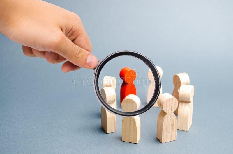 Het vergrootglas bekijkt de Mensentribune in een cirkel op een grijze achtergrond Mededeling Commercieel team, groepswerk, team stock afbeelding