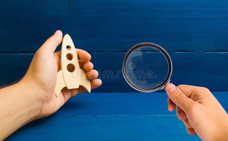 Het vergrootglas bekijkt de ontwikkeling van kosmische ruimte Blauwe houten achtergrond Opleiding, spel Raket in hand concept E royalty-vrije stock foto