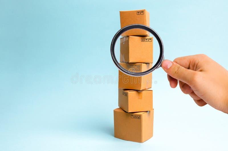 Het vergrootglas bekijkt de Toren van kartondozen op een blauwe achtergrond Het concept zich het bewegen en levering van goederen royalty-vrije stock afbeelding