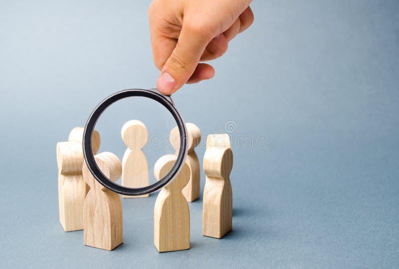 Het vergrootglas bekijkt mensentribune in een cirkel op een grijze achtergrond Houten cijfers van mensen Een cirkel van mensen stock afbeelding