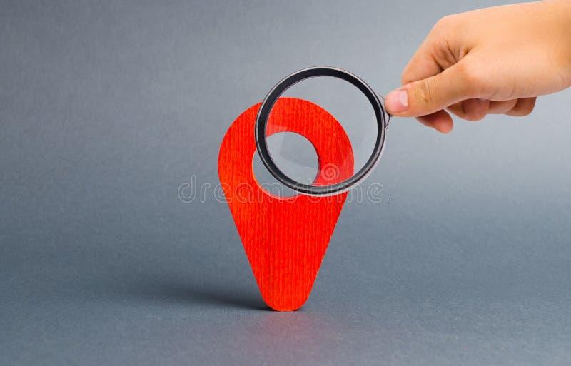 Het vergrootglas bekijkt rode wijzerplaats op een grijze achtergrond Concept navigatie en trefpunt met nadruk op de Verrekijkers stock afbeeldingen