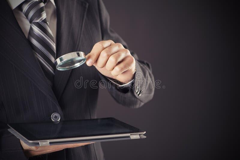Het vergrootglas en de tablet van de zakenmanholding stock fotografie