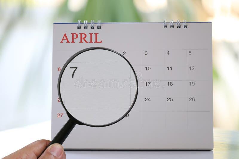 Het vergrootglas ter beschikking op kalender u kan Zevende dag van kijken stock foto