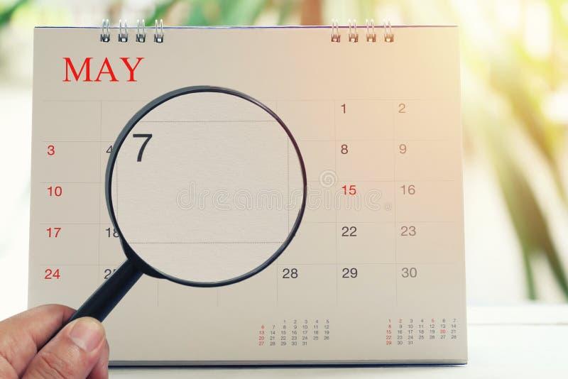 Het vergrootglas ter beschikking op kalender u kan Zevende dag van kijken stock afbeelding
