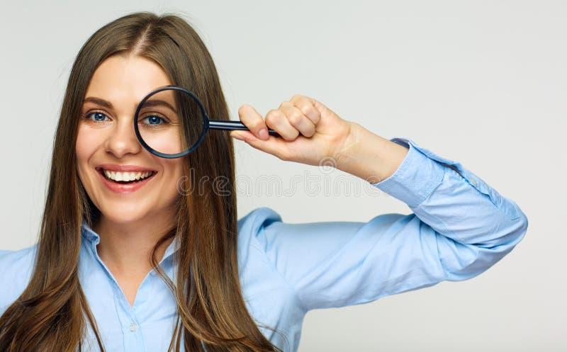 Het vergrootglas van de bedrijfsvrouwenholding achter ogen stock fotografie