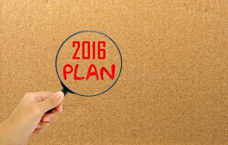 Het vergrootglas van de handholding met het nieuwe jaar van het woorden 2016 plan stock afbeeldingen