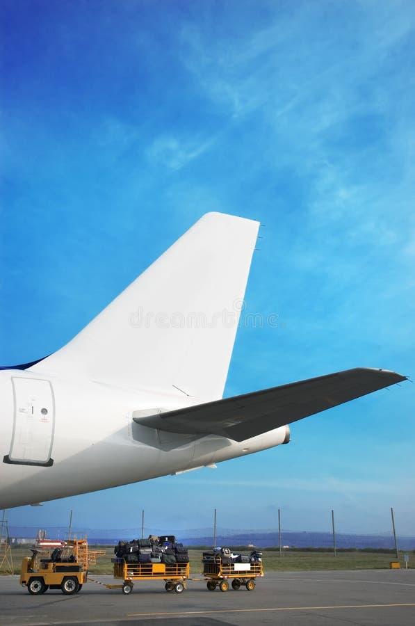 Het verhaal van Airplain en bagagekar stock afbeelding