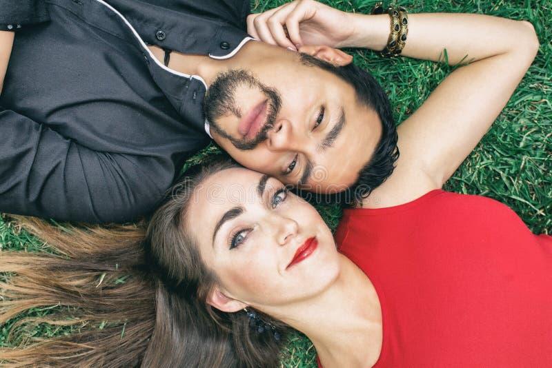 Het verhaal van de liefde Een donkerbruine man en een mooie donkerbruine vrouw liggen op het gras royalty-vrije stock afbeelding