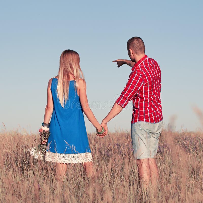 Het verhaal van de liefde Mooi jong paar die in weide lopen, openlucht royalty-vrije stock afbeeldingen