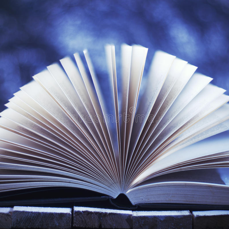 Het Verhaal van de winter Open boek op vage blauwe achtergrond stock afbeeldingen