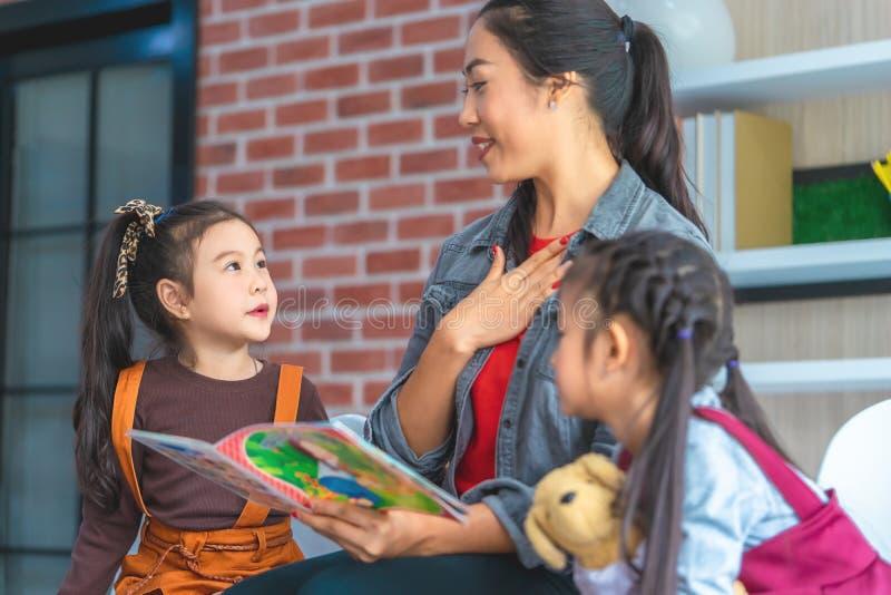 Het verhaalboek van de leraarslezing aan kleuterschoolstudenten stock afbeelding