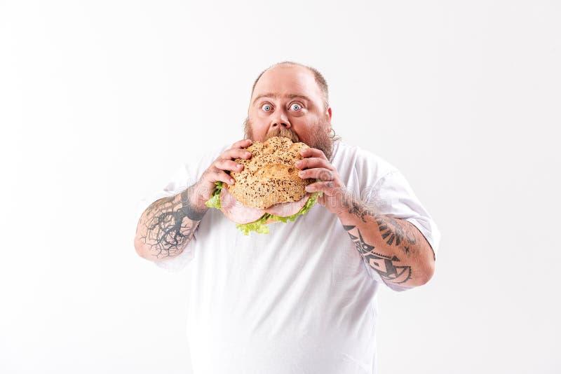 Het verhongeren van de dikke mens die grote hamburger bijten royalty-vrije stock afbeelding