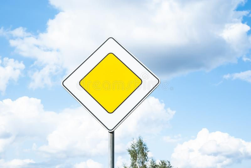 Het verkeersprioriteit van de verkeerstekenhoofdweg tegen blauwe hemelachtergrond stock foto
