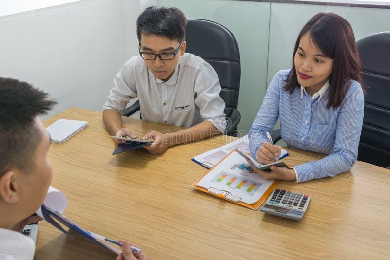 Het verkoopteam analyseert financieel document in vergaderzaal royalty-vrije stock afbeelding