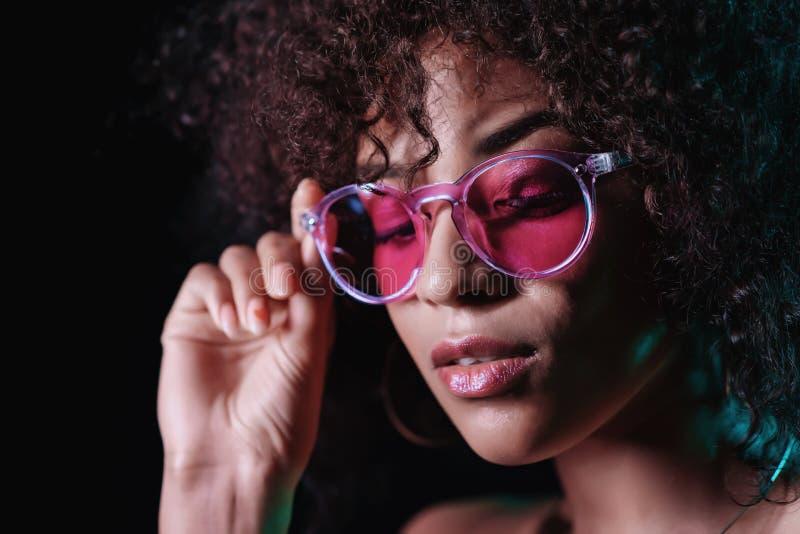 Het verleidelijke ongebruikelijke meisje met krullend afrohaar verbetert haar glazen Sexy vrouw die met perfecte make-up camera b royalty-vrije stock foto