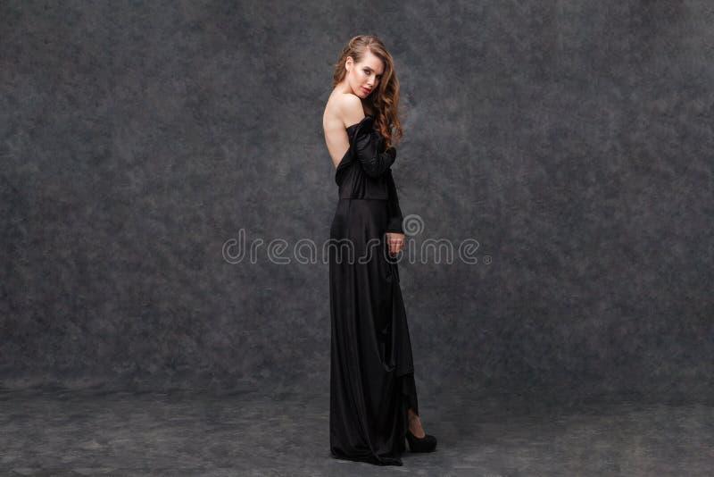 Het verleiden van mooie vrouw in lange zwarte kleding met open rug royalty-vrije stock foto