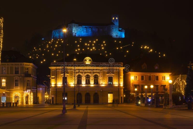 Het verlichte die kasteel van Ljubljana boven Congresvierkant voor Kerstmis wordt verfraaid stock fotografie