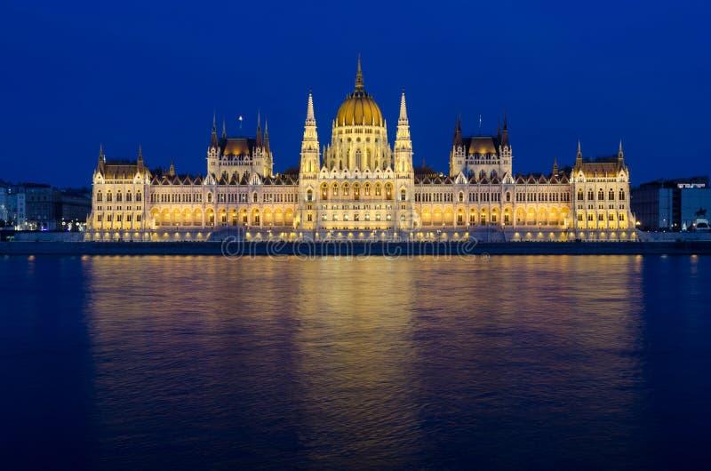 Het verlichte Hongaarse die Parlement van Boedapest bij nacht in de rivier van Donau wordt weerspiegeld stock foto