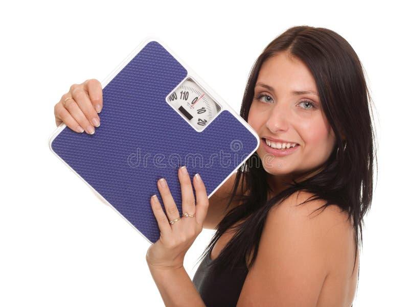 Het verliesvrouw van het gewicht op gelukkige schaal stock foto's