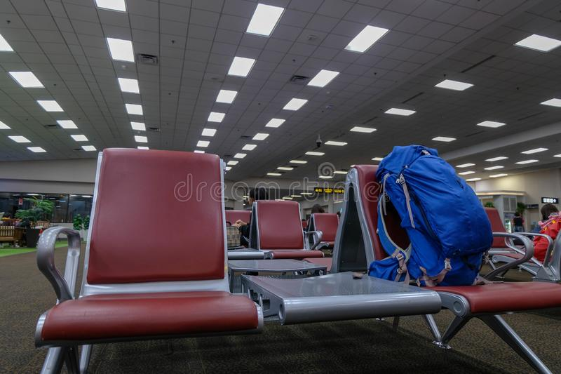 Het verlof van de rugzakzak op de stoel in eindluchthaven die op het inschepen tijd wachten stock foto's