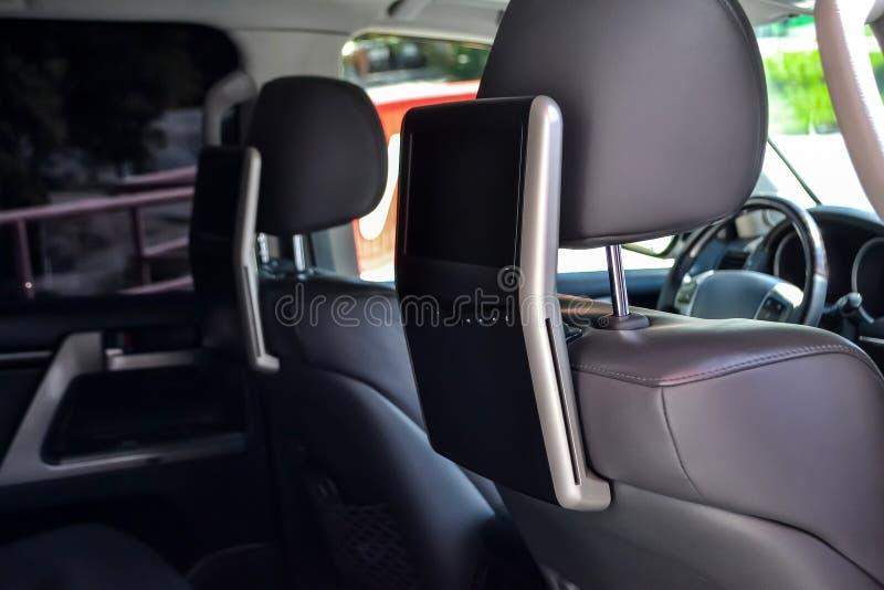 Het vermaaksysteem voor achterpassagiers in een auto met twee monitors zette op de ruggen van de voorzetels voor het letten op TV royalty-vrije stock afbeelding
