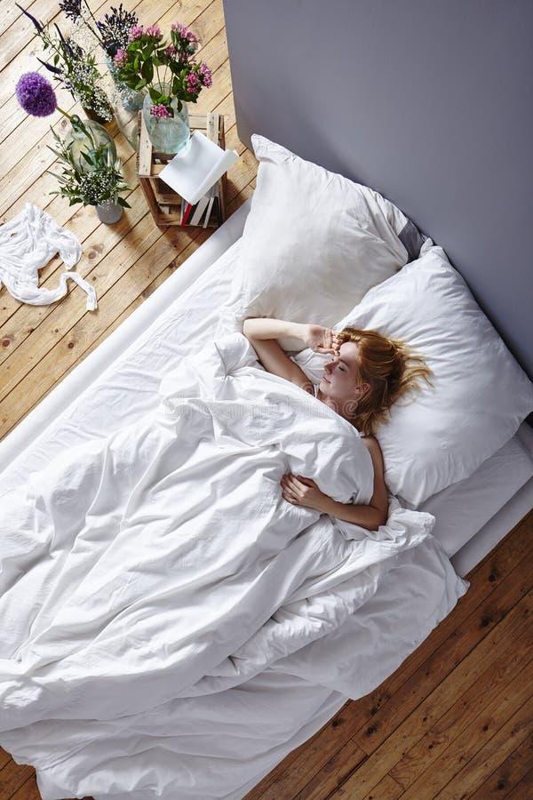 Het vermijden van de vrouw van de ochtendzon in bed royalty-vrije stock foto