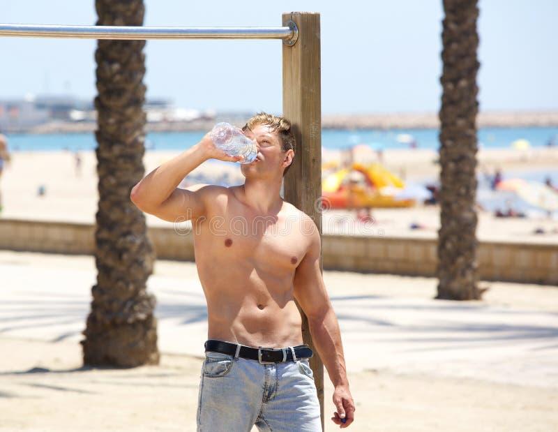 Het vermoeide drinkwater van de geschiktheids jonge mens na training stock afbeeldingen