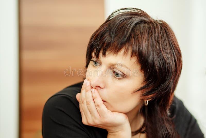 Het vermoeide hoofd van de vrouwenholding, die uit eruit zien stock afbeeldingen