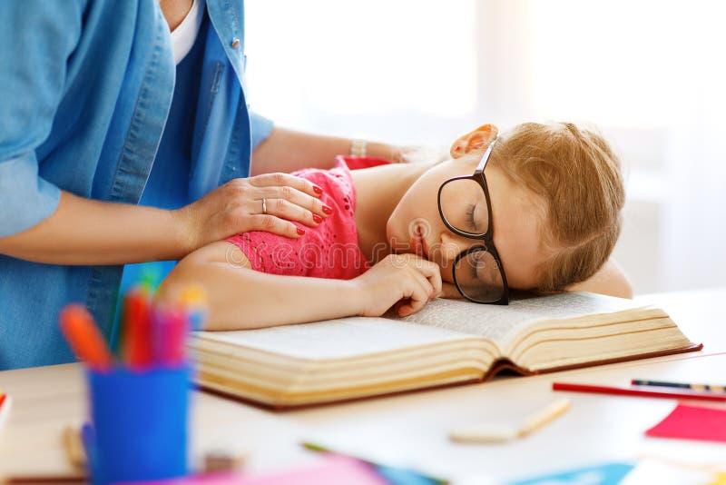 Het vermoeide kindmeisje viel in slaap toen zij haar thuiswerk thuis deed royalty-vrije stock foto's
