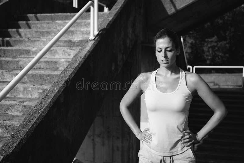Het vermoeide sportieve jonge vrouw rusten royalty-vrije stock afbeeldingen