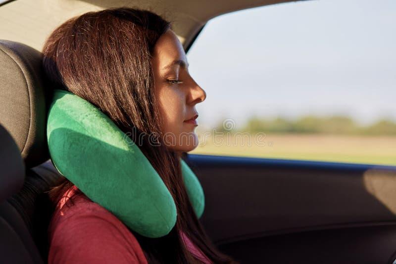 Het vermoeide vrouwelijke de reishoofdkussen van het reizigersgebruik, slaap in auto, dekkingslange afstand, voelt comfort voor h royalty-vrije stock foto