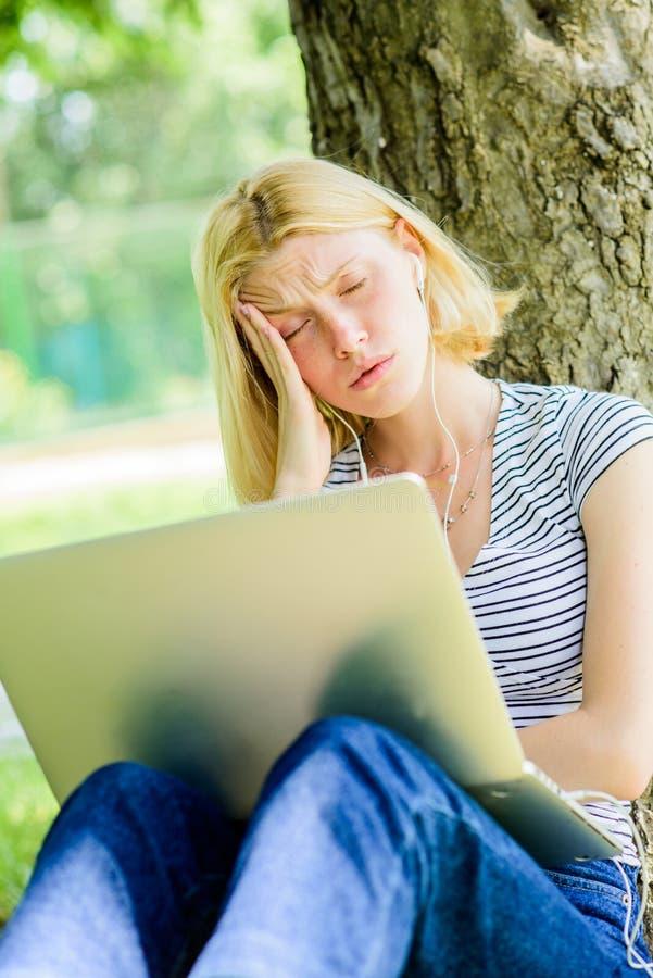 Het vermoeide vrouwenwerk aangaande laptop Het studentenleven Mooie vrouw Online Onderwijs de student treft voor examens voorbere stock fotografie
