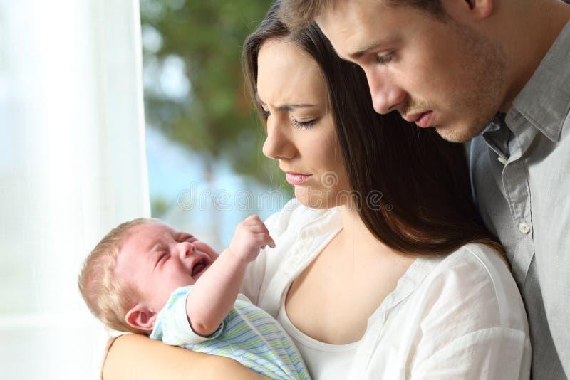 Het vermoeide wanhopige ouders en baby schreeuwen stock foto's