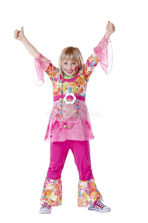 Het vermomde jonge meisje glimlacht en houdt duimen tegen stock foto's