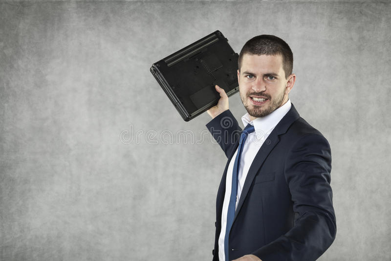 Het vernietigen van computer, boze bedrijfsmens stock foto